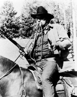 John Wayne on horseback reins in his mouth guns at ready True Grit