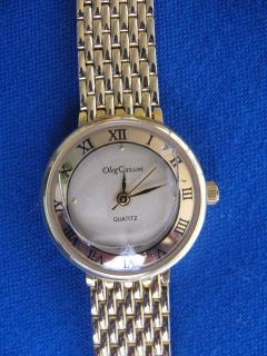 Ladies goldtone white round faced Oleg Cassini quartz watch