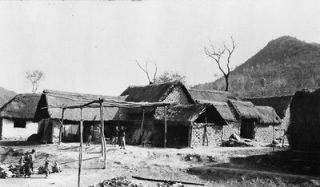 c1918 photo China  mud brick houses with thatch roofs, people in yard